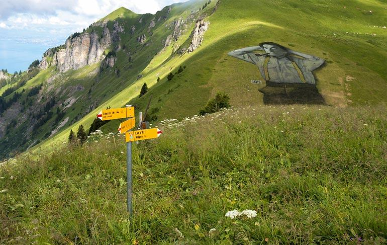 Известный французский художник Гийом Легро, работающийпод псевдонимом Saype, создал в горах швейцарского города Лейзин необычный ленд-арт на площади 10 000 квадратных метров.  Saype нарисовал на траве гигантского человека, лежащего на склоне горы. Закинув руки за голову и закрыв глаза, он отдыхает под яркими лучами солнца и курит трубку.